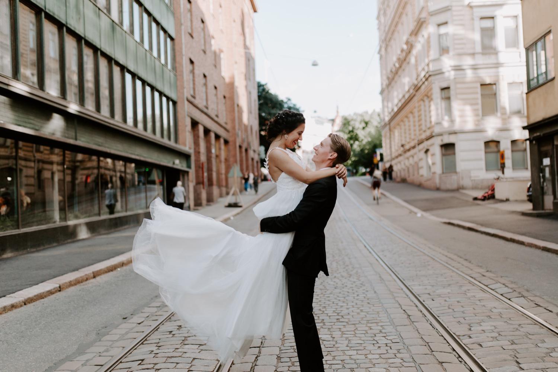 Punavuori hääkuvat. Groom lifting bride in city centre. Hääkuvaaja Helsinki.