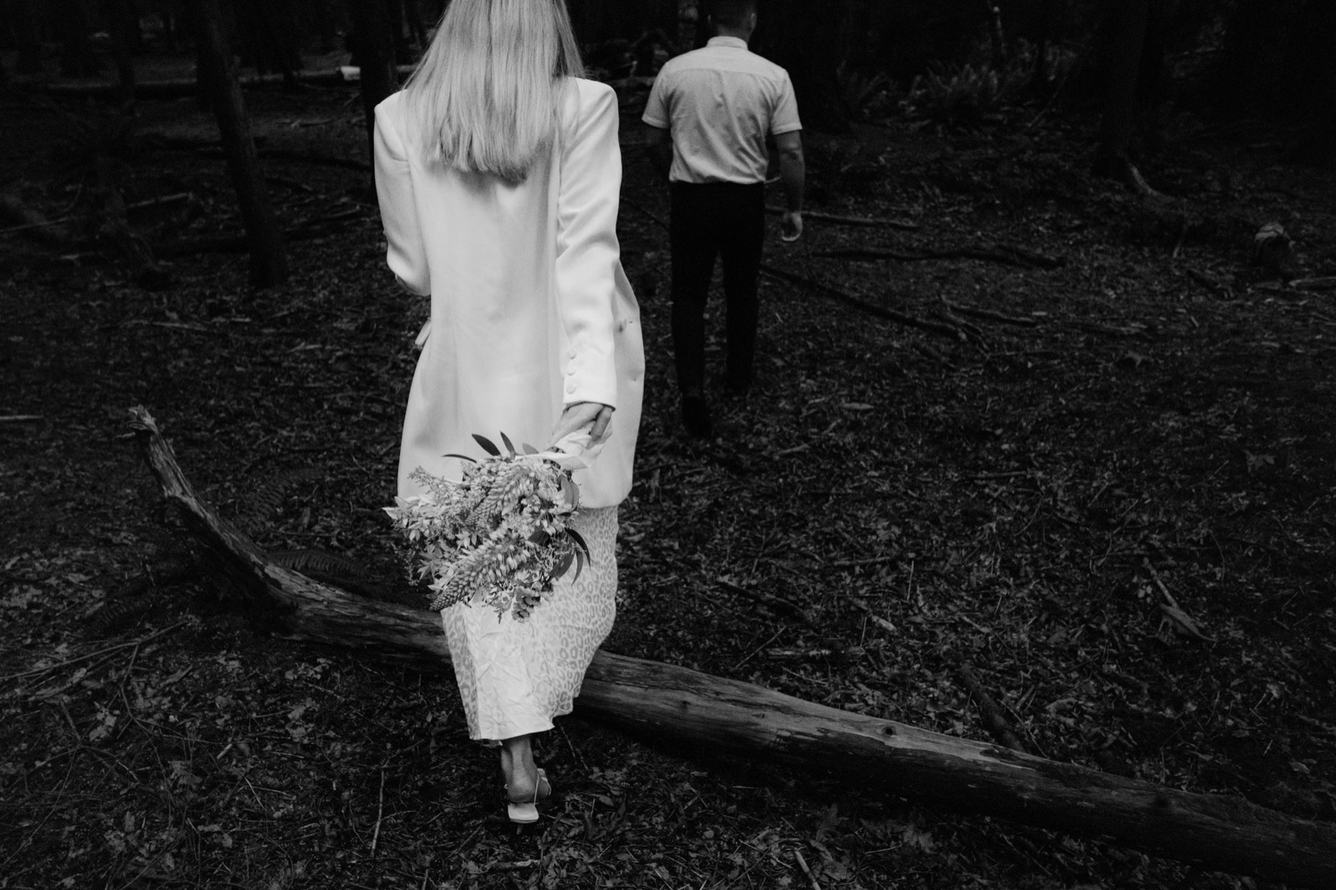 bride holding bouquet while walking away in pacific spirit park
