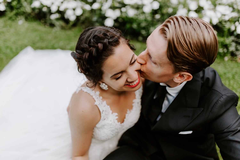 Groom kissing bride on the cheek sitting in park. Helsinki hääkuvaaja. Helsinki wedding photographer.
